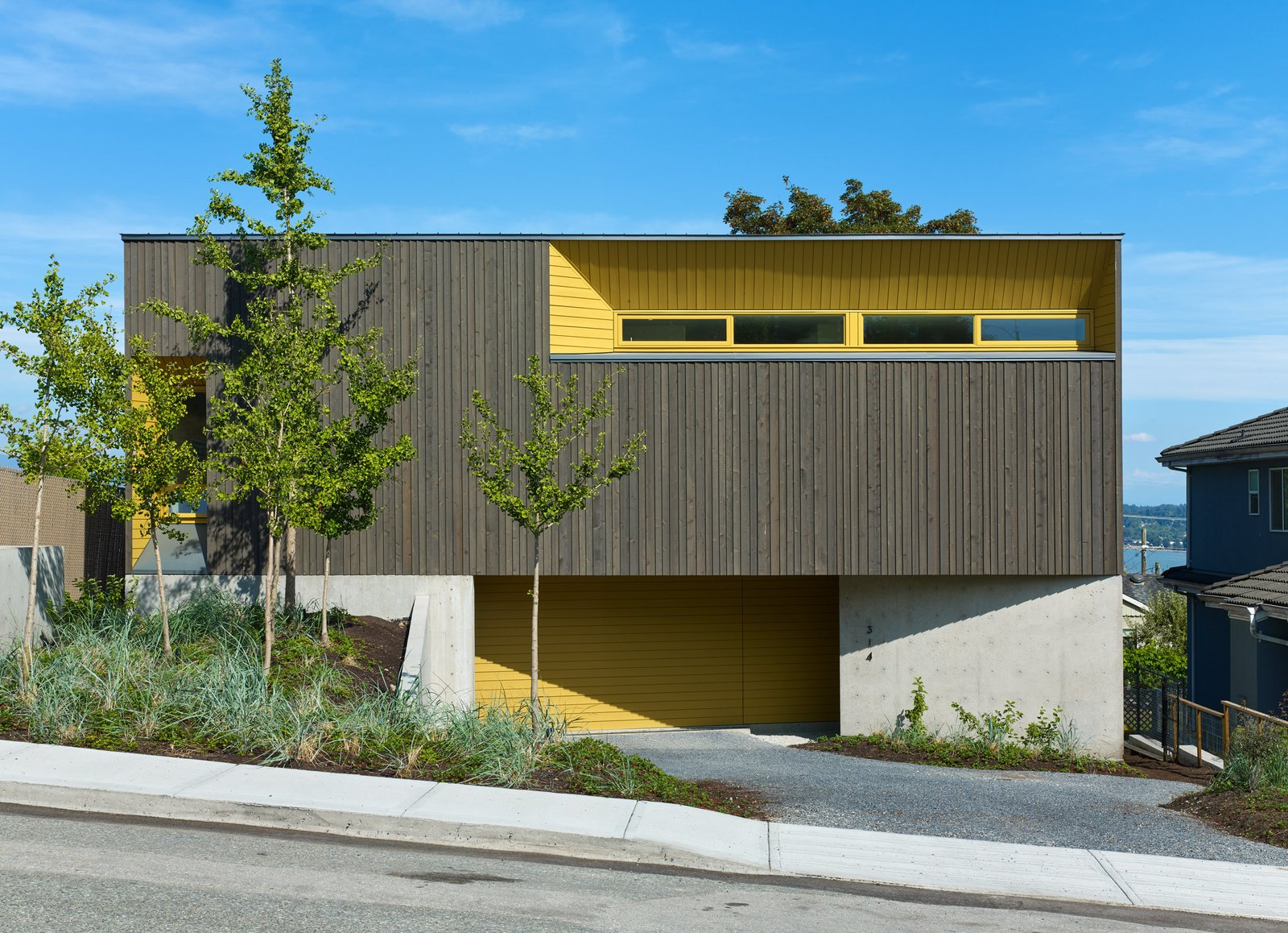 Exterior, Concrete Siding Material, House Building Type, and Wood Siding Material The exterior is clad in stained cedar and painted channel siding; the Turmeric shade was selected to complement the hue of the ginkgo trees in the front yard.  Photo 3 of 6 in A Suburban Vancouver Home Edits its Privacy Settings