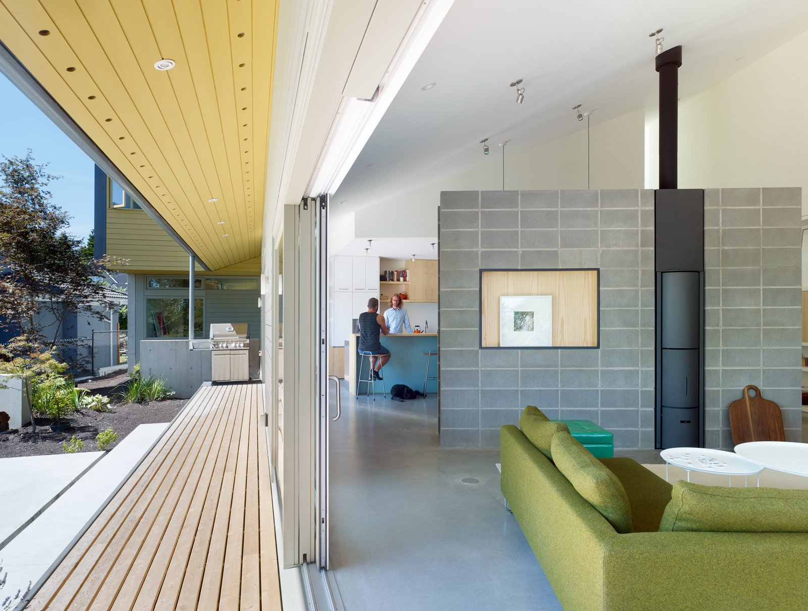 Living Room, Sofa, and Concrete Floor Sliding doors by Mountainview unite the garden and interior of a residence in British Columbia. The underside of the deck overhang is covered in Benjamin Moore's Turmeric paint, a shade also used on the house's front facade. A Canyon sofa by Bensen joins Fat Fat tables by Patricia Urquiola for B&B Italia in the living room; a cinderblock wall with a stove by Stûv divides the space from the kitchen.  Photo 2 of 6 in A Suburban Vancouver Home Edits its Privacy Settings