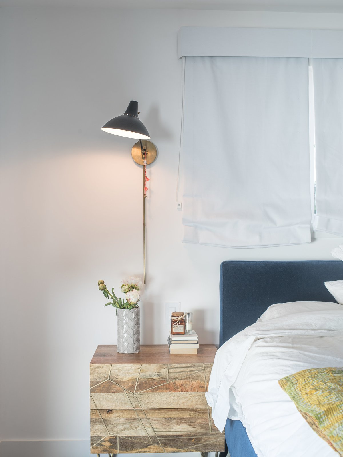 """Bedroom, Bed, and Table Lighting A downstairs guest bedroom is a welcome retreat for visitors. """"Because I do so much traveling, if someone comes to stay, I want them to feel they can just be,"""" says Lena. The Roar + Rabbit brass-inlaid nightstand is from West Elm.  Bedrooms by Dwell from Lena Headey's Off-Camera Castle"""