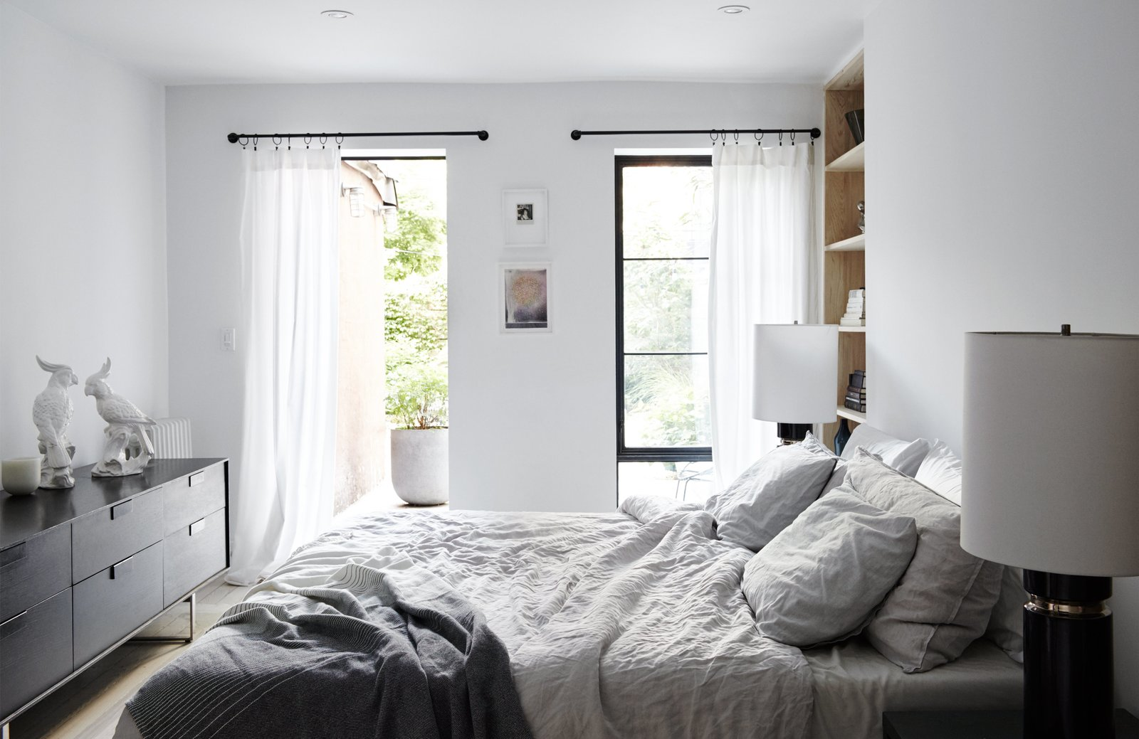 Madelena-Gnewikow Residence bedroom with black and white accents and built-in shelving beside the bed.