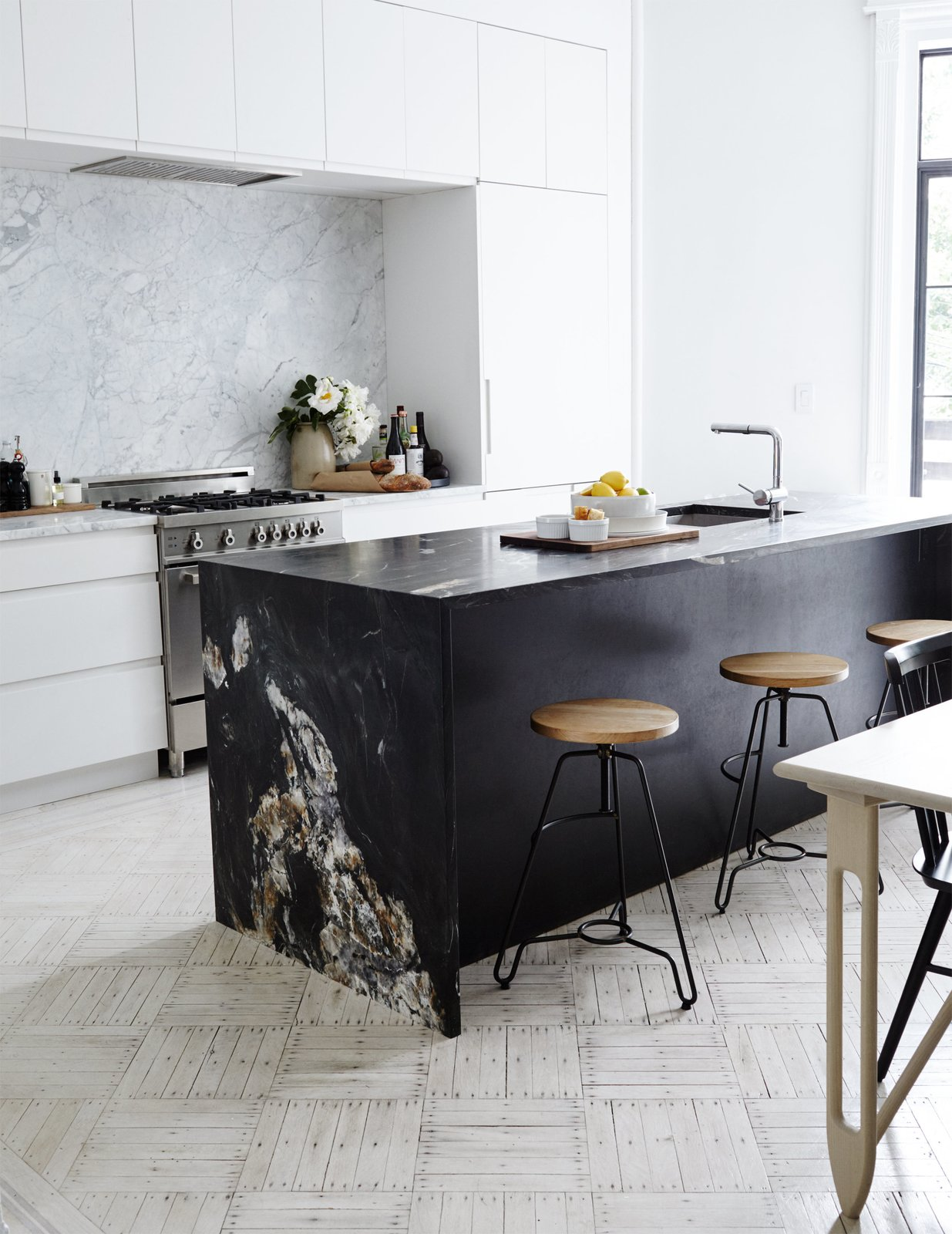 Madalena-Gnewikow Residence kitchen with matte-black natural patterned quartzite island in front of sets of white kitchen cabinets and counters and backsplash dressed with white quartzite.