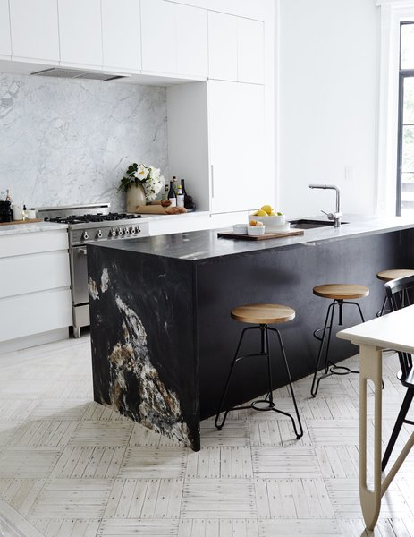 The couple removed an ornamental fireplace mantle in the kitchen, one of few period details they decided not to keep, due to its size. Matte-black quartzite slabs from ABC Worldwide Stone form the kitchen island, which is outfitted with Blanco fixtures; a white Carrara backsplash frames the Bertazzoni range and Dunsmuir cabinetry. The oak-and-steel bar stools are from ABC Carpet & Home.
