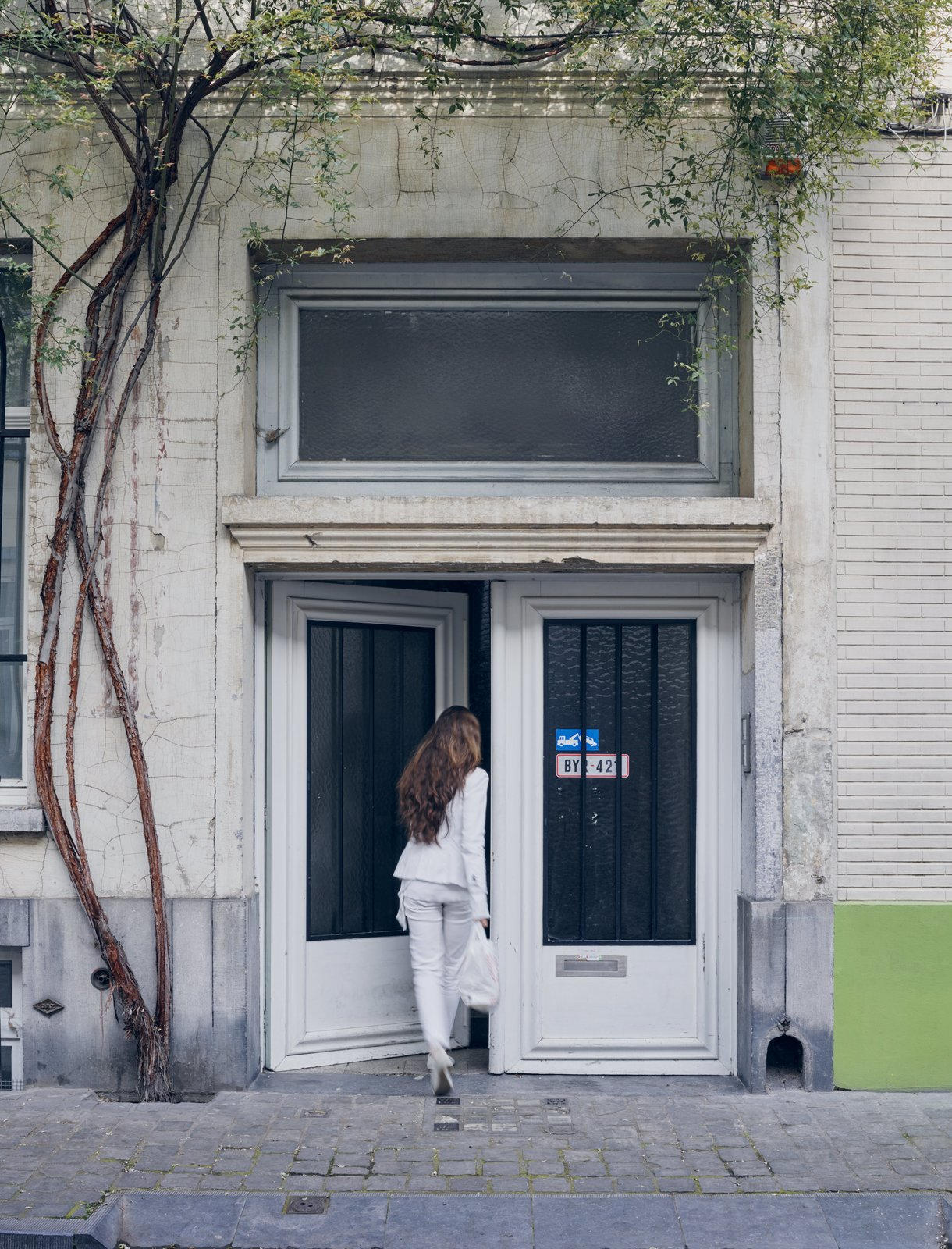 Exterior Venlet's wife and business partner, Evi Lippens, enters the home's unassuming street entrance in the city's Flemish Dansaert district.  Photo 6 of 11 in Futuristic Forms Meet Historical Details in Designer Danny Venlet's Brussels Home