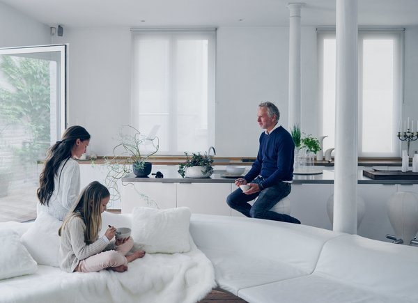 A palette of white-on-white textures and materials defines the living room. Venlet is joined by Lippens and their daughter, Nylah-Noy, on the Bendy Bay sectional—a modular, undulating fiberglass frame topped with leather cushions that he produced for Viteo in 2007. Cast-iron columns original to the structure, lacquered IKEA cabinets, and a custom stainless-steel countertop lined with a variant of Venlet's Burdekin barstools make up the galley-style kitchen.