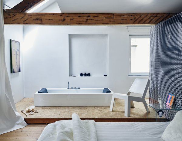Prolific Dutch designer Danny Venlet rebuilds his roost in Brussels. A spare layout marks the master suite on the third floor. The rectangular KOS bathtub, integrated into an elevated plywood platform, pairs with Gert Van Der Vloet's Cut Low lounge in Corian. The couple used elements of a photo they took of one of Venlet's designs to create the graphic wall covering.