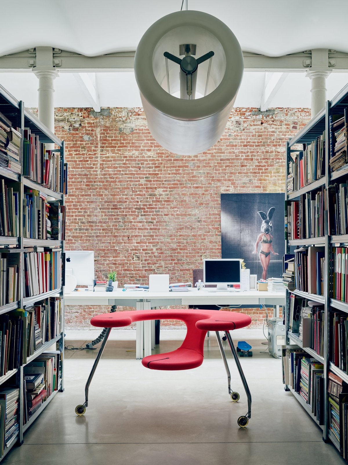 Office, Library Room Type, Shelves, Desk, and Chair Recalling the form of an airplane engine, his cylindrical D2V2 pendant hovers above his sculptural Easy Rider, a mobile desk-seat hybrid set on castors.  Photo 10 of 11 in Futuristic Forms Meet Historical Details in Designer Danny Venlet's Brussels Home
