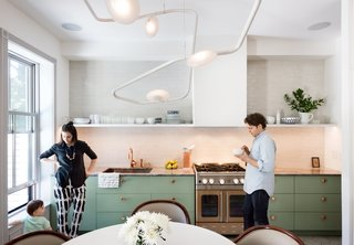 The couple's bold mix-and-match sensibility applies most unconventionally to the material palette; nearly every surface is different from the next. The cook station pairs a copper Watermark faucet with an Italian marble countertop, a copper-toned stainless-steel range from Blue Star, and a backsplash of masonry Foundation Brick tile by Ann Sacks.