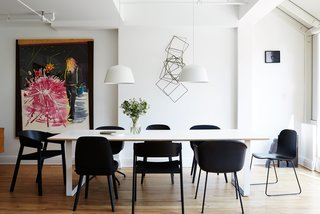A series of black Muuto chairs—Fiber, Cover, Nerd, and Visu—surrounds a 70/70 table and white Ambit pendants, both by TAF Architects for Muuto.