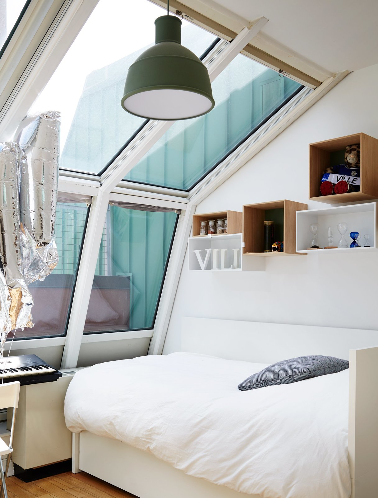 Bedroom, Ceiling Lighting, Pendant Lighting, Shelves, Storage, Bookcase, Bed, Chair, Lamps, and Medium Hardwood Floor A Muuto Unfold pendant hovers over one of the kids' beds.  Photo 11 of 14 in A Danish Design Kingpin Moves to NYC With a Shipping Container of Furniture in Tow