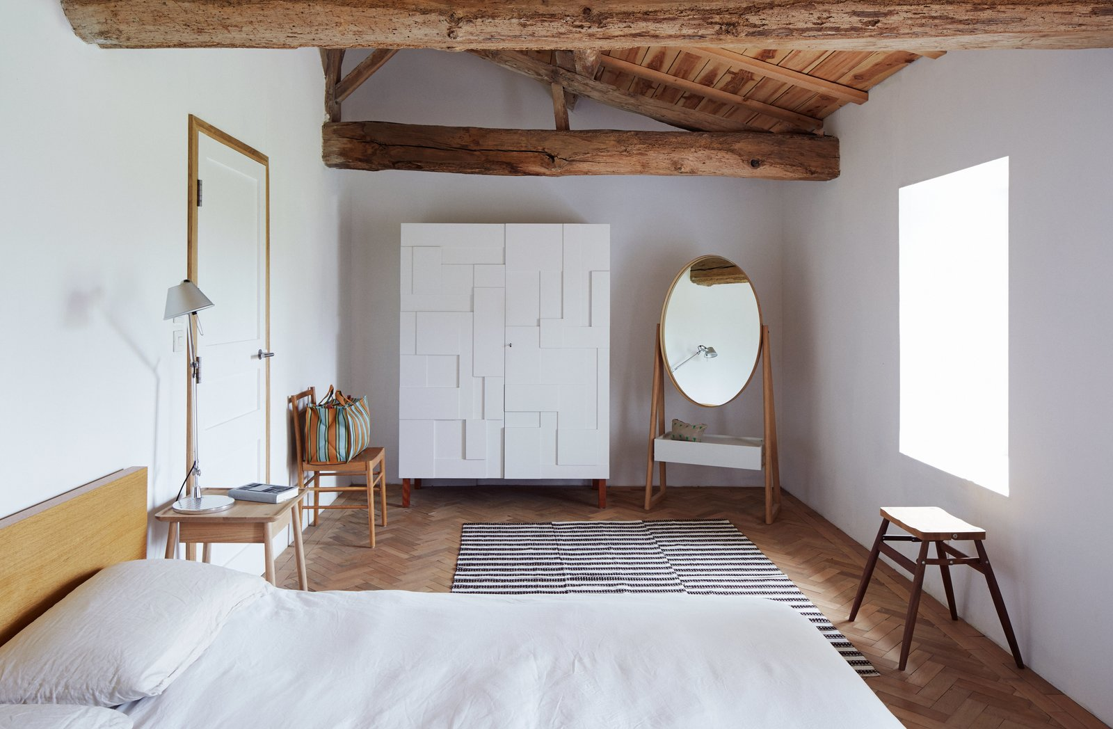 Pinch-Bannon Residence bedroom with chevron wood floors and exposed beam ceilings.