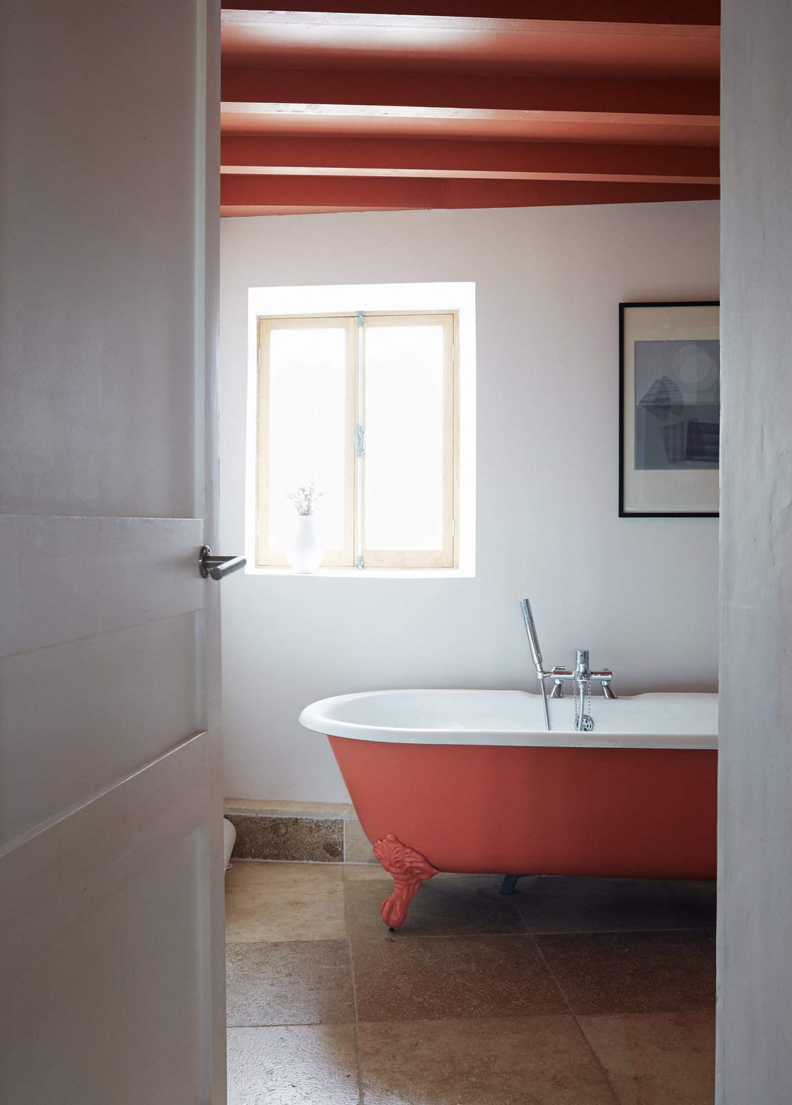 Pinch-Bannon Residence bathroom with sliding windows and orange painted ceilings with exposed beams.