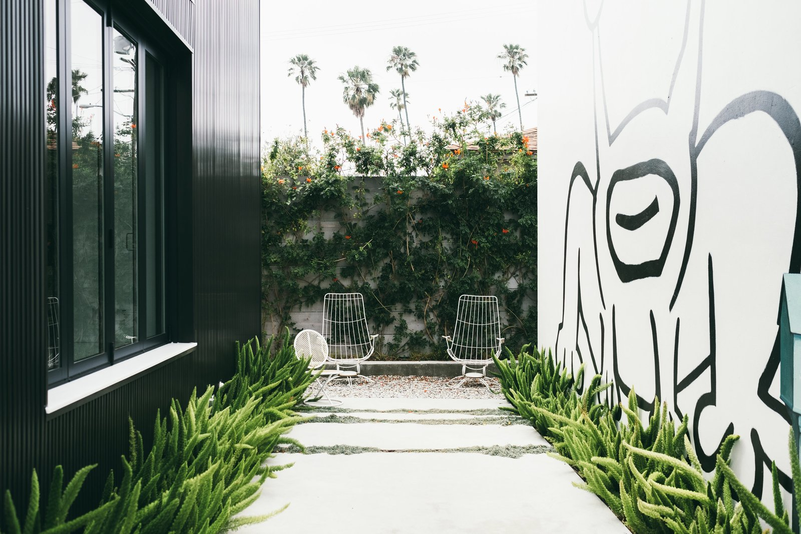 A giant mural by the artist Daniel Johnston dominates the outdoor garden of an art-filled home in Venice designed by Chris Rudin.  Photo 2 of 9 in The Home Tours of Dwell on Design 2016