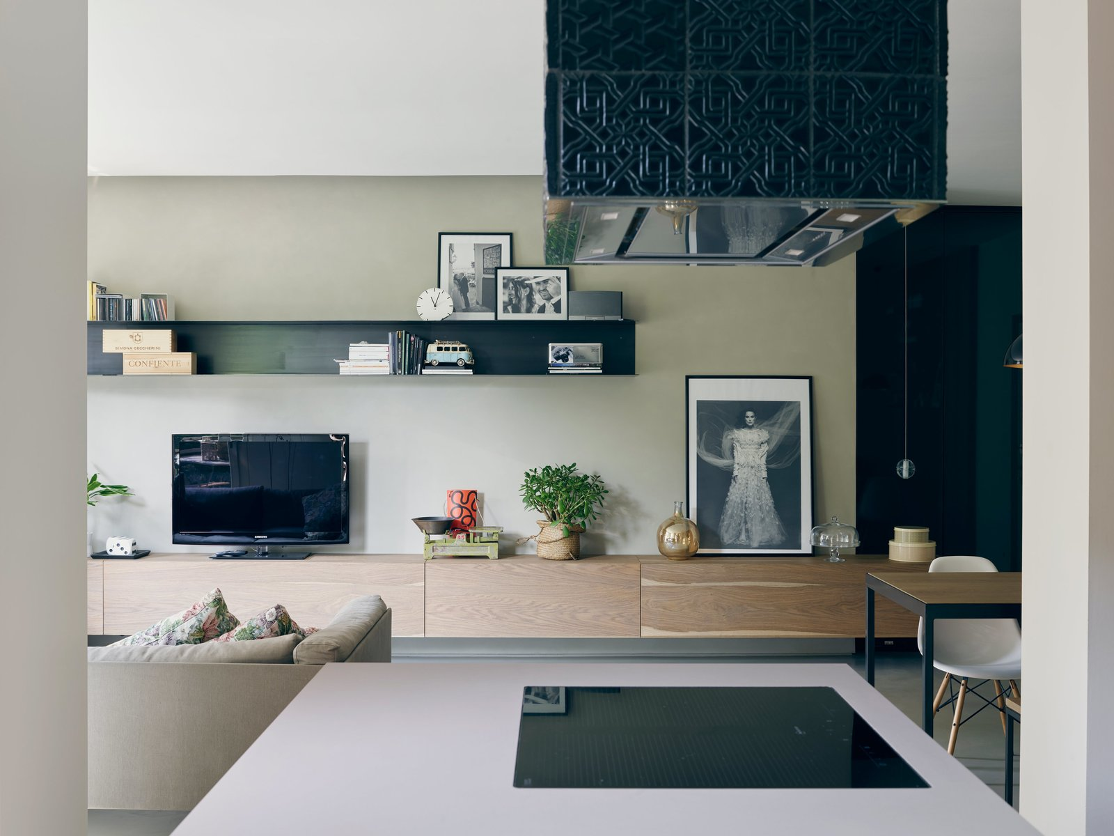 Living Room, Chair, Sofa, Storage, Bookcase, Shelves, and Concrete Floor A suspended oak sideboard runs the length of the living room. The project leads designed that piece and the black-painted metal shelves on the wall; both were fabricated by Giuseppe Motta,a local artisan. A 14.1 pendant by Omer Arbel for Bocci hangs near one end.  Photo 6 of 15 in This Growing Family Maximizes Every Last Inch in Their 850-Square-Foot Apartment