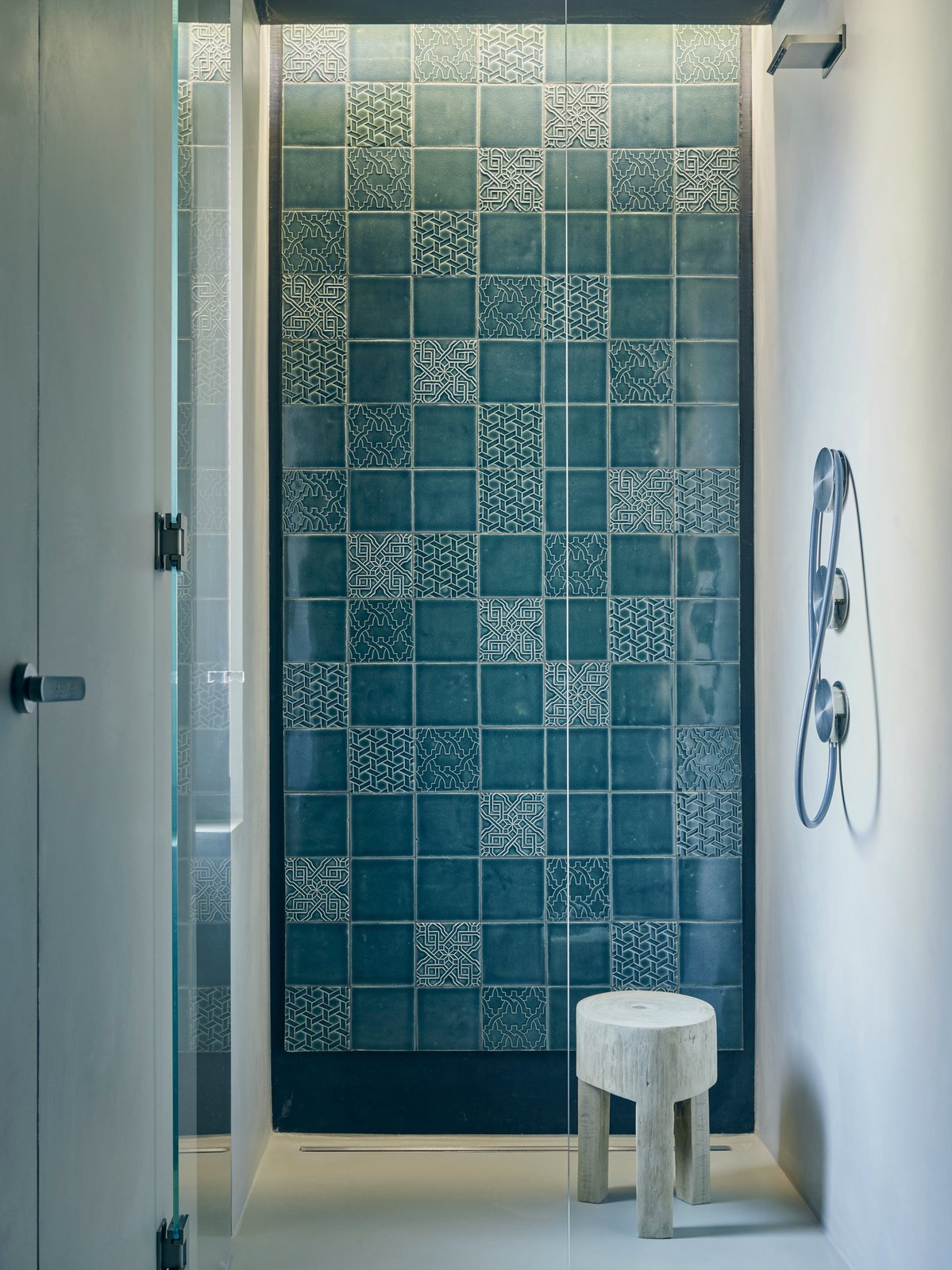 """Bath Room and Open Shower Tucked in a corner of the master bedroom, a curbless shower with Cea fixtures showcases a wall of patterned Italian tiles that coordinate with those used on the range hood in the kitchen.The designers sought to imbue the apartment's minimalist framework with a handcrafted touch. """"We wanted to add natural and warm elements to the palette,"""" Di Stefano says.   Photo 10 of 15 in This Growing Family Maximizes Every Last Inch in Their 850-Square-Foot Apartment"""