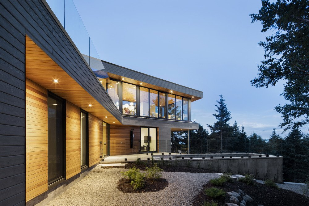 Exterior, Concrete Siding Material, and Wood Siding Material The entire house is clad in a grey wood facade.  Photo 2 of 6 in A Home Inspired by the Stars Soars Off the Ground