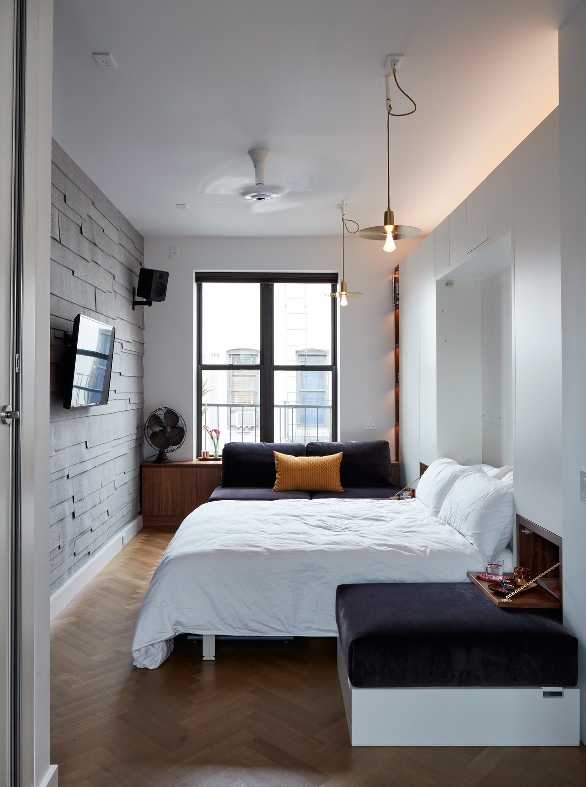 Bedroom, Bed, Shelves, Lamps, Light Hardwood Floor, Ceiling Lighting, Pendant Lighting, and Storage At night, the living-dining area converts into the primary bedroom.  Photo 12 of 16 in At His 350-Square-Foot Apartment, Small Space Champion Graham Hill Practices What He Preaches