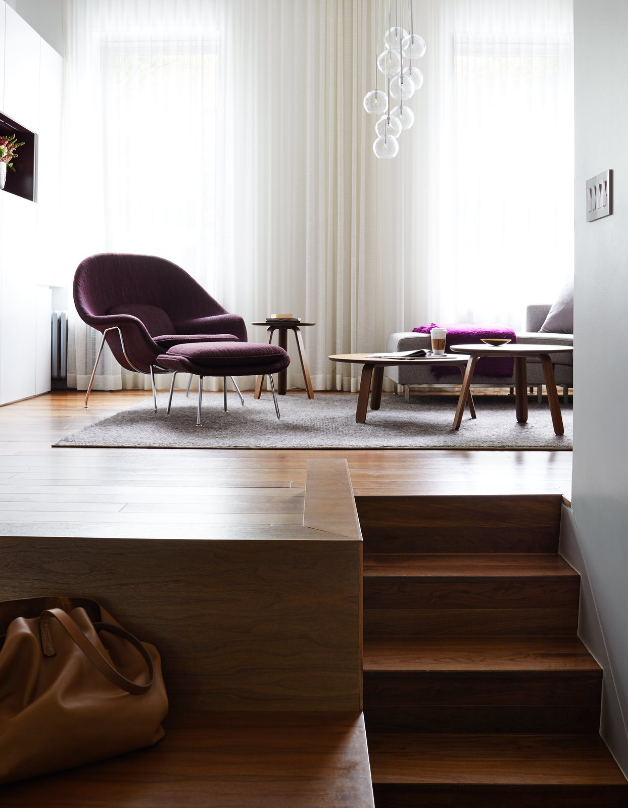 Living Room, Chair, Medium Hardwood Floor, Coffee Tables, Sectional, Pendant Lighting, End Tables, and Rug Floor The unusual layout of René Roupinian's Upper West Side home is what initially attracted her to the space, but the three-level plan proved difficult to organize. In his first solo project as STADT Architecture, Christopher Kitterman used a palette of walnut and white to unify the apartment, which he filled with space-saving solutions. Near the entrance, a Goliath table from Resource Furniture can expand to seat up to 10.  Photo 5 of 5 in Editor's Letter: Small Space, Big Design