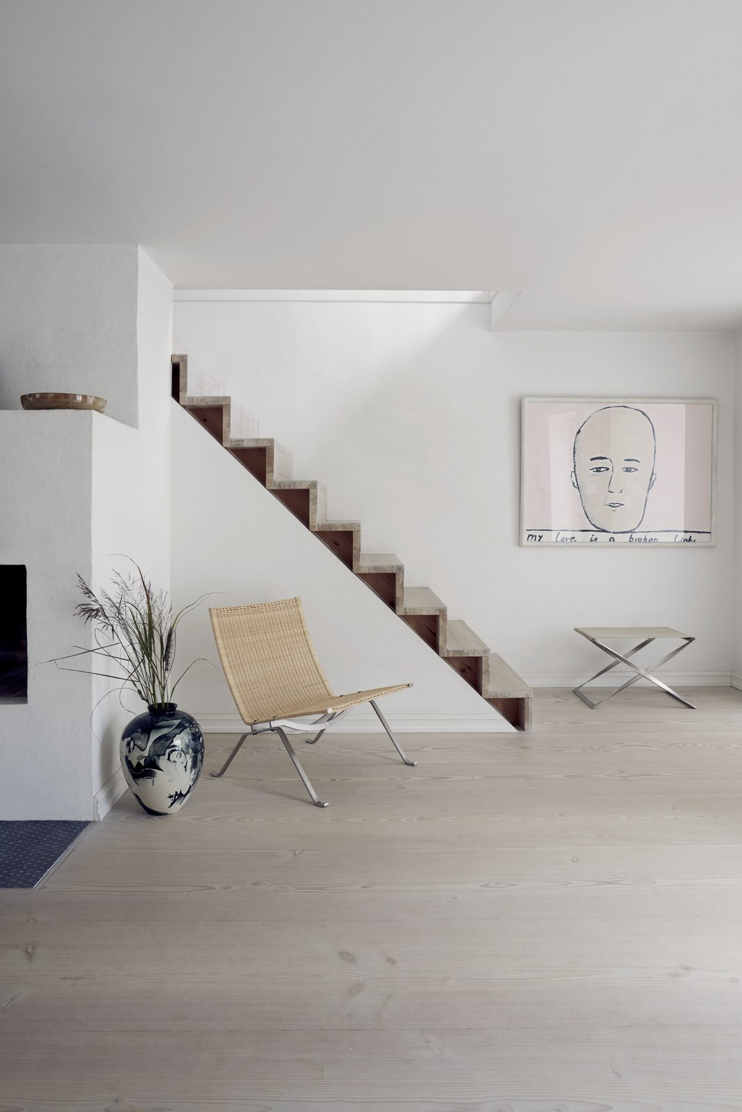 The wicker PK22 lounge chair and a foldable PK91 stool made from steel and canvas sit by the staircase on the first floor.  Stairs from A Recent Trip Leaves Us Dwelling on Denmark