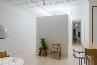 A custom whitewashed oak mirror, White paint by Benjamin Moore, and a lighting program by Melanie Freundlich carry the brightness throughout the loft. The Grid sofa is by Resource Furniture. The public spaces are separated from the private bedrooms by the new Sheetrock addition.