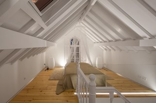 The bedroom on the top floor features exposed beams and minimal furnishings.