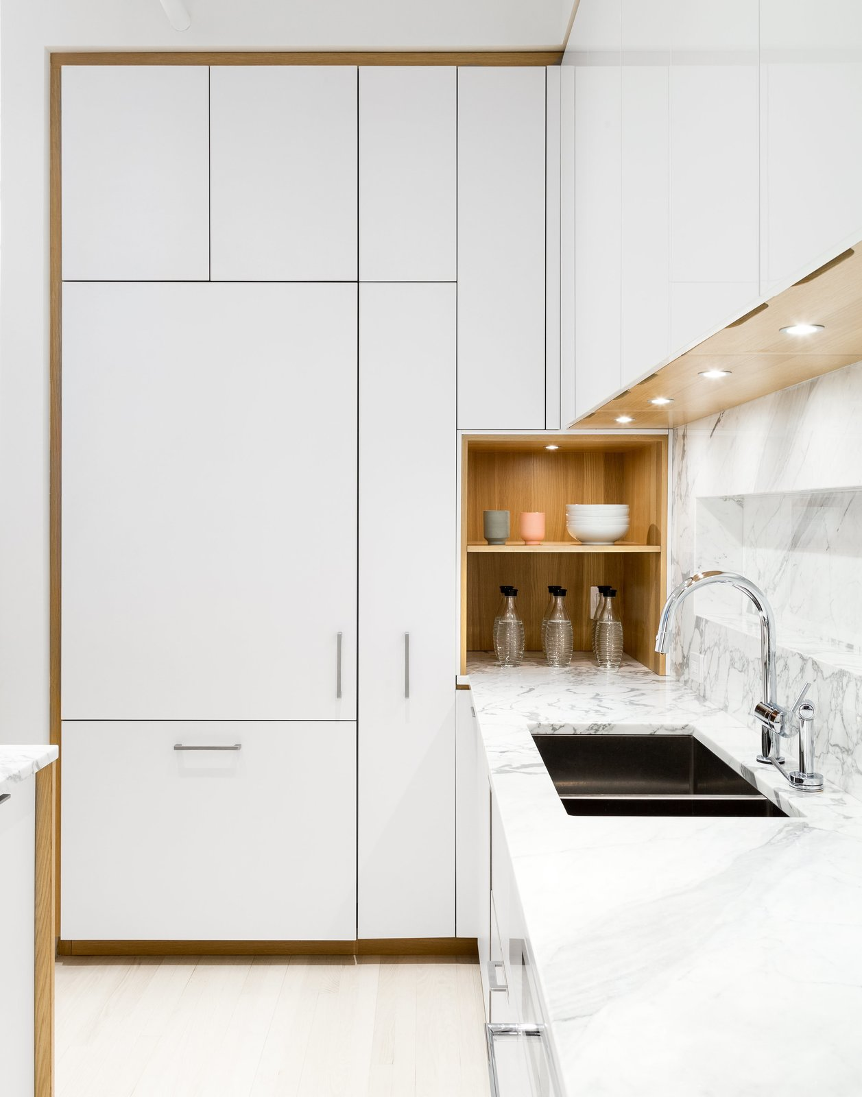 Kitchen, White Cabinet, Undermount Sink, Marble Counter, Marble Backsplashe, Accent Lighting, Light Hardwood Floor, Recessed Lighting, and Refrigerator The kitchen has been designed in collaboration with Henrybuilt. The laminate cabinets are paired with a marble countertop by SMC Stone.    Photo 24 of 30 in These 30 White Kitchens Are Anything But Ordinary from This 60-Square-Foot Structure Divides and Conquers in a Manhattan Renovation