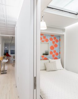 "Across from it, a Murphy bed by Resource Furniture—lined with Camilla Meijer wallpaper and featuring a customized niche—allows the space to function as a guest room. An electric Velux skylight frames views of the original tin plates above. The architects chose to leave space between the top of the structure and the ceiling to maintain the rectangular proportions of the loft. ""It reads right away,"" Singer says of the volume. ""It's very satisfying."""