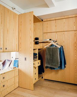 Stowing the queen-size Room Makers Murphy bed by SICO frees up access to custom built-in cabinets and pull-down closet rods by Hafele that illuminate when the door is opened.