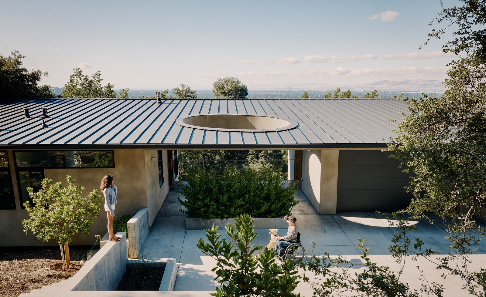 Exterior, House Building Type, Stucco Siding Material, and Metal Roof Material Resident Elizabeth Twaddell enjoys the weather with her daughter Uma outside the guesthouse Neal Schwartz designed for her mother-in-law, Surendra, who frequently visits for extended stays. A concrete driveway forks off from the main house to lead to a covered breezeway, sited between the new 775-square-foot structure and a two-car garage.  Best Photos from A Family Guesthouse Made for Accessibility, Aging in Place—and That View