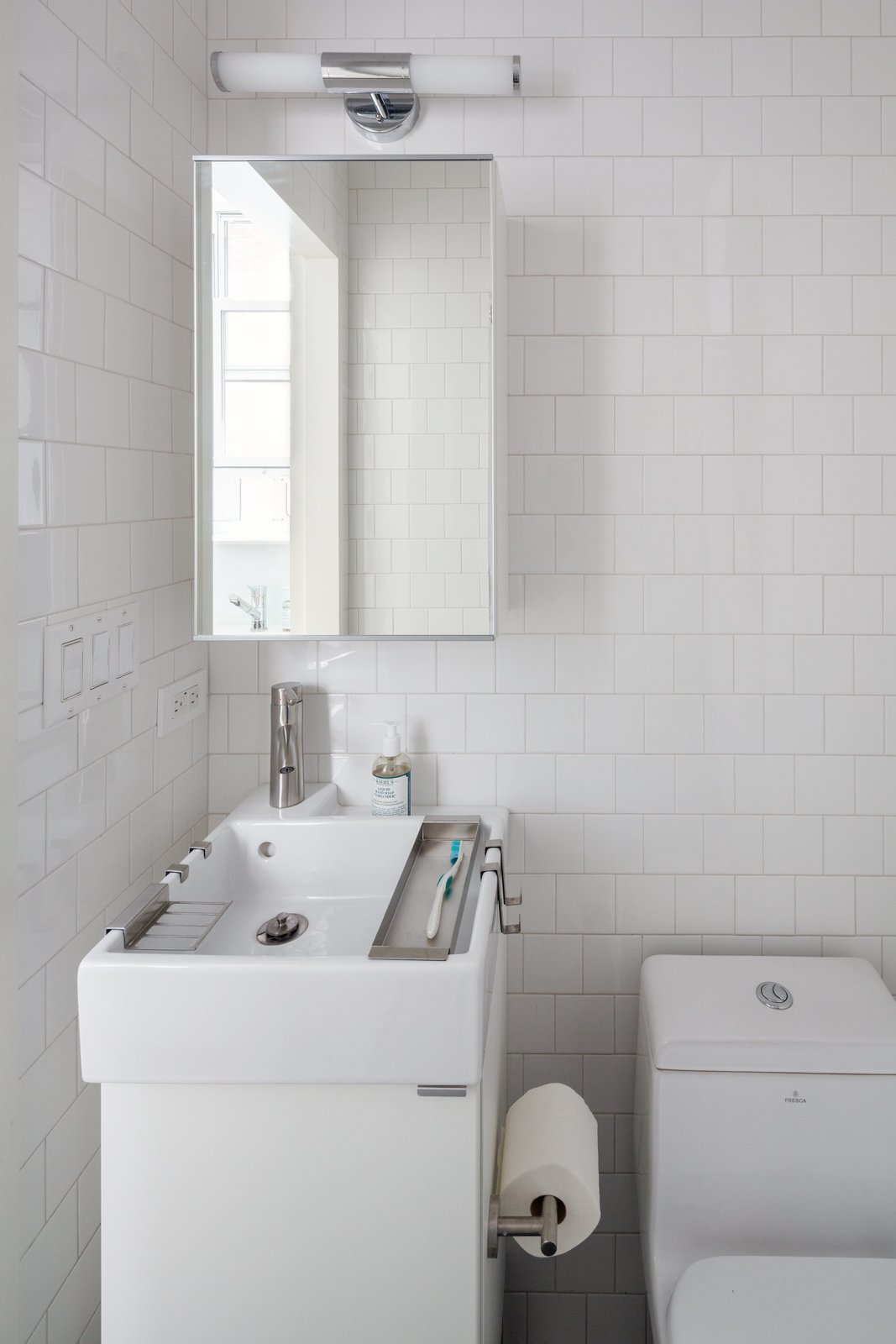 Bath Room, Drop In Sink, Vessel Sink, and One Piece Toilet In the bathroom, a compact Lillången sink from IKEA offers a narrow profile for the tight space, yet is deep enough to accommodate hanging storage trays for toiletrie. The toilet is by Fresca and the subway tile is from Mosa.  Photo 9 of 10 in This 390-Square-Foot Renovation Is Compact Yet Comfortable in Greenwich Village
