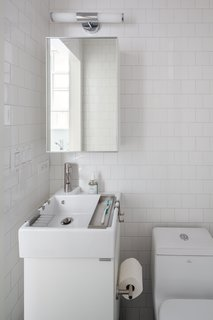 In the bathroom, a compact Lillången sink from IKEA offers a narrow profile for the tight space, yet is deep enough to accommodate hanging storage trays for toiletrie. The toilet is by Fresca and the subway tile is from Mosa.
