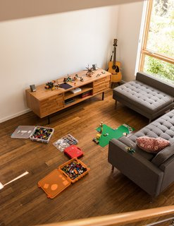 "Chris and Wendy Kozina live with their son, Ben, in a ""Tallis"" style town house. They selected bamboo floors for the 1,155-square-foot, two-bedroom interior. The family strives to cap their possessions at 500 items—Legos not included. In the living room, an Innes media cabinet from Room & Board is paired with a Gus Modern sectional."