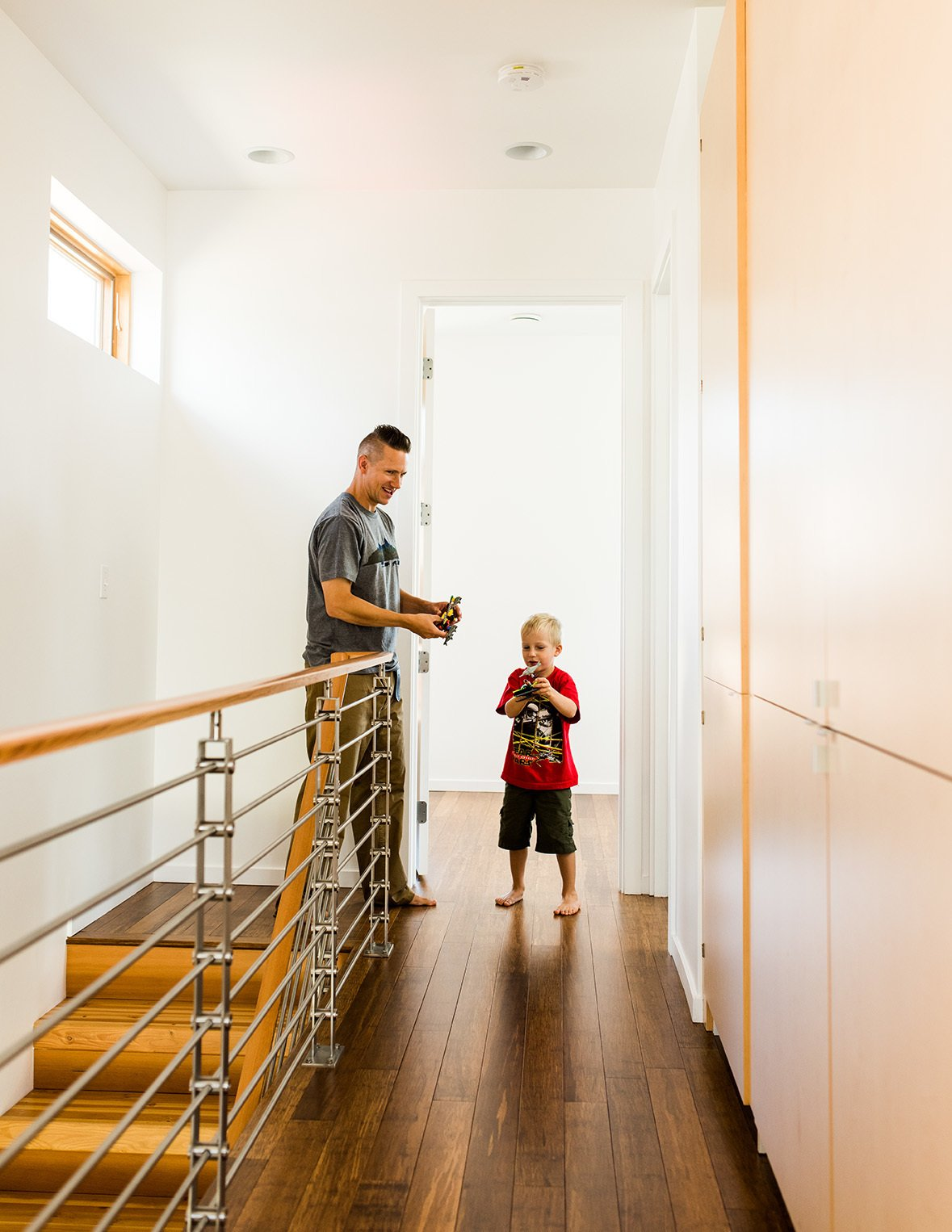 Hallway and Medium Hardwood Floor On the upstairs landing, Chris and Ben pause by an IC Railings system from Issaquah Cedar and Lumber.  Photo 13 of 15 in It Takes a Village