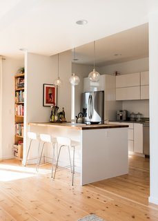 """Marja Preston's family lives in one of Grow's """"Everett"""" houses, with three bedrooms in 1,846 square feet. In their kitchen, West Elm pendants hang over a counter of myrtle butcher block sourced from Green Home Solutions."""