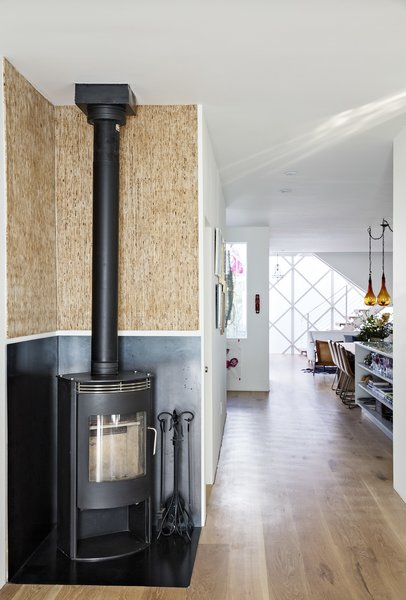 Upcycled Kirei wall board pairs with a Rais Gabo stove in the original part of the house, which connects seamlessly  to the prefab addition.