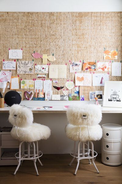 Industrial stools covered in sheepskin sit at the art nook off the dining area. Sydney's artworks line the Kirei wall panels.