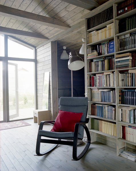 Near a Gent wood-burning stove by Thorma in the living area, an IKEA Poäng chair and ottoman provide a cozy spot for reading. Thanks to the passive design strategies utilized by Ovchinnikov, the house stays warm through the winter with only minimal heating required.