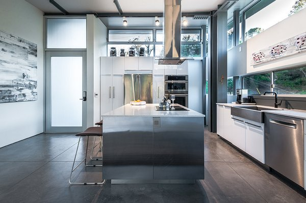 The house is laid out on three levels, with the main entrance leading to the top-floor kitchen, which features concrete floors, quartz counters, a refrigerator and wall oven by Electrolux, and a stainless-steel apron-front sink from Kraus.