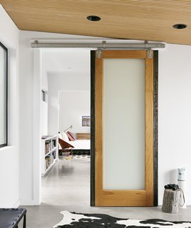 Pops of color and warm materials, like the sliding wooden barn doors from Simpson, provide a cozy contrast to the polished concrete floors throughout.