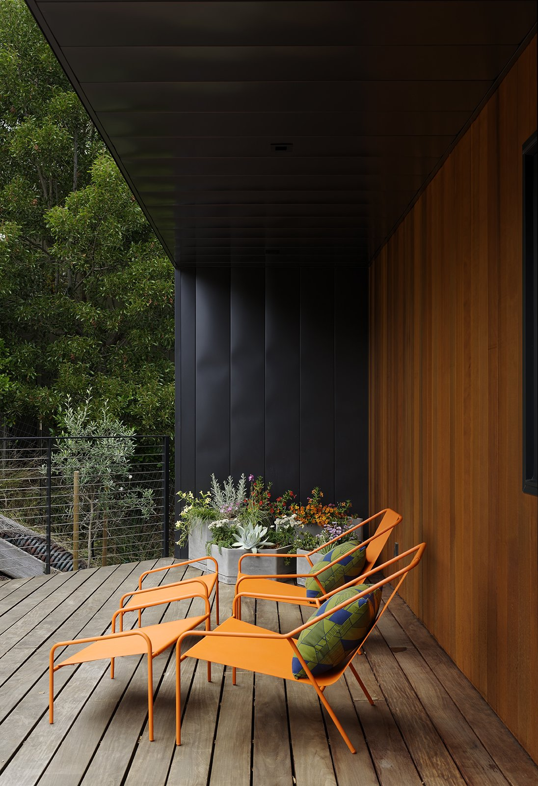 Outdoor and Wood Patio, Porch, Deck Together with Nick Dine, Chris also designed the concrete planters, pillows, and powder-coated steel lounge chairs on the front deck; all are part of the Modern by Dwell Magazine home collection for Target. Predominantly native, fire-resistant plantings dot the property, which sits in a wildland urban inter-face (WUI) zone.  Photo 2 of 15 in Moving Mountains