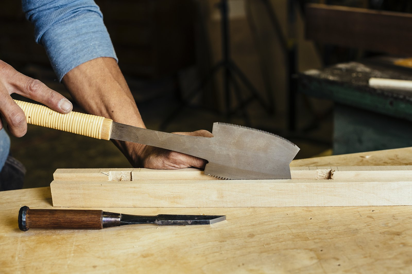 Using a Japanese handsaw, the woodworker, in just one stroke, cuts a channel into the wood,  creating a slot for the rice paper.  Photo 5 of 9 in How to Shape a Shoji, Step by Step
