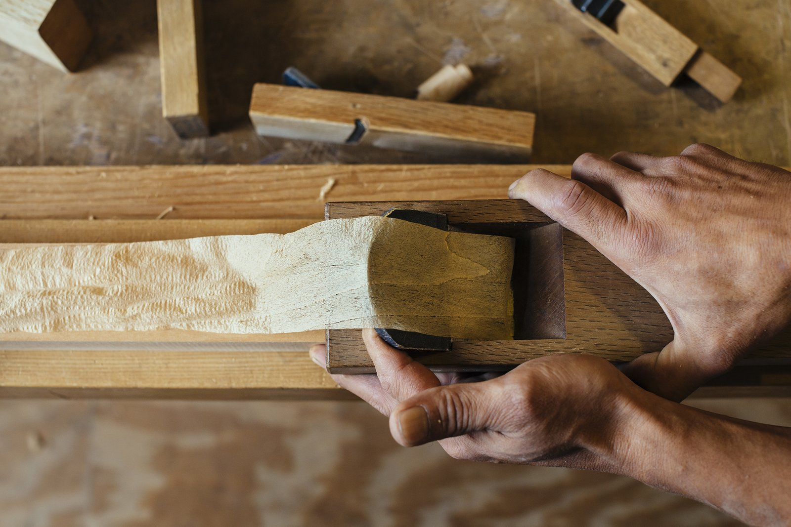 Hamada carefully pulls a  plane along the wood's surface. He will use only one stroke  to make sure that the surface  is even. It is never sanded.  Photo 7 of 9 in How to Shape a Shoji, Step by Step