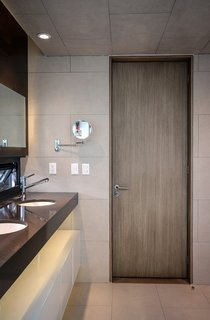 The door is made of MDF panels attached  to a wood frame and topped with an ash veneer. The tiles are from Spanish brand Vives.