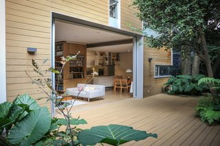 """Floor-to-ceiling aluminum doors slide into the walls, bringing the outside world in and doubling the size of the living room. """"It converted the space into something truly extraordinary, surrounded by vegetation. The climate in Mexico is perfect for it,"""" says Nina."""