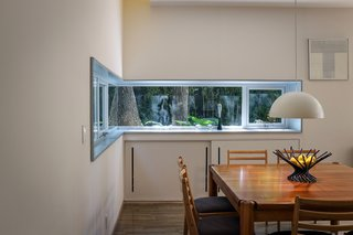 The dining area's aluminum window frame was custom cut onsite to wrap around  a corner.