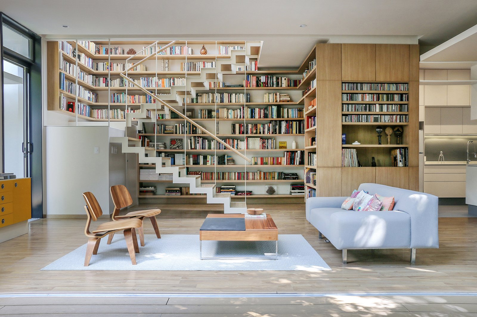 Living, Shelves, Rug, Chair, Sofa, Coffee Tables, Light Hardwood, and Bookcase A pair of Molded Plywood lounge chairs by Charles and Ray Eames for Herman Miller sit opposite a BoConcept coffee table and a sofa of Paul's design. For his father's book collection, Paul created a library around the double-height staircase.  Best Living Bookcase Light Hardwood Photos from Retired Couple Build Modern in Mexico City
