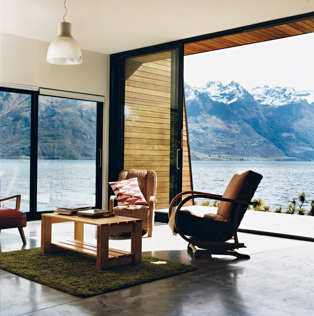 Living Room, Chair, Concrete Floor, Coffee Tables, and Pendant Lighting The main living area. The home is flanked on the east by a precipitous mountain range named The Remarkables. In summer, the weather gets hot enough for the family to go swimming and boating.  Drift Bay House