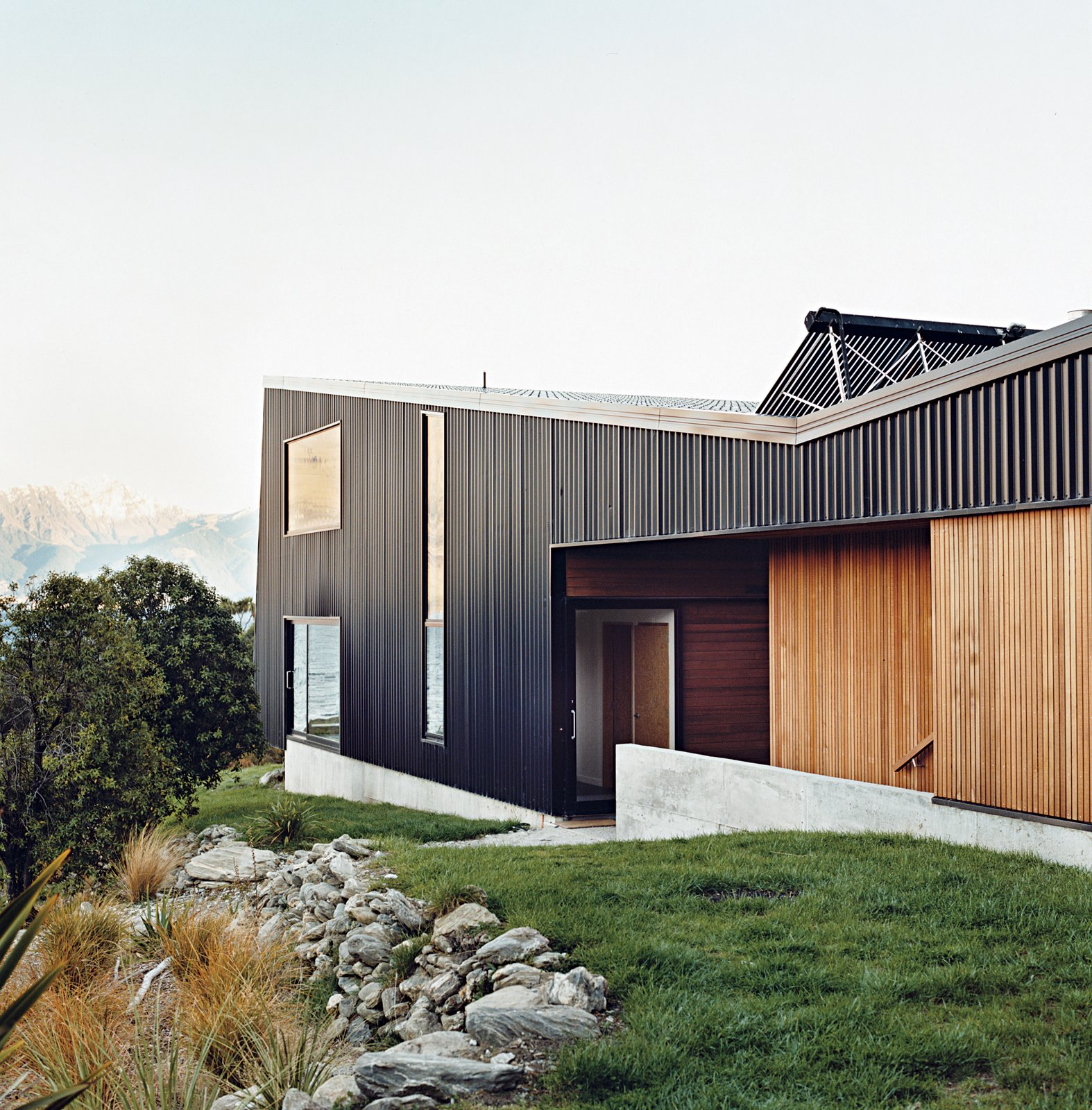 "Exterior, Metal Siding Material, House Building Type, Metal Roof Material, and Wood Siding Material The home is mostly clad in black trapezoidal-profile steel, with cedar boards lining what the owners call the ""human spaces""—external passages between buildings. A solar hot water system perches on the roof.  Drift Bay House"