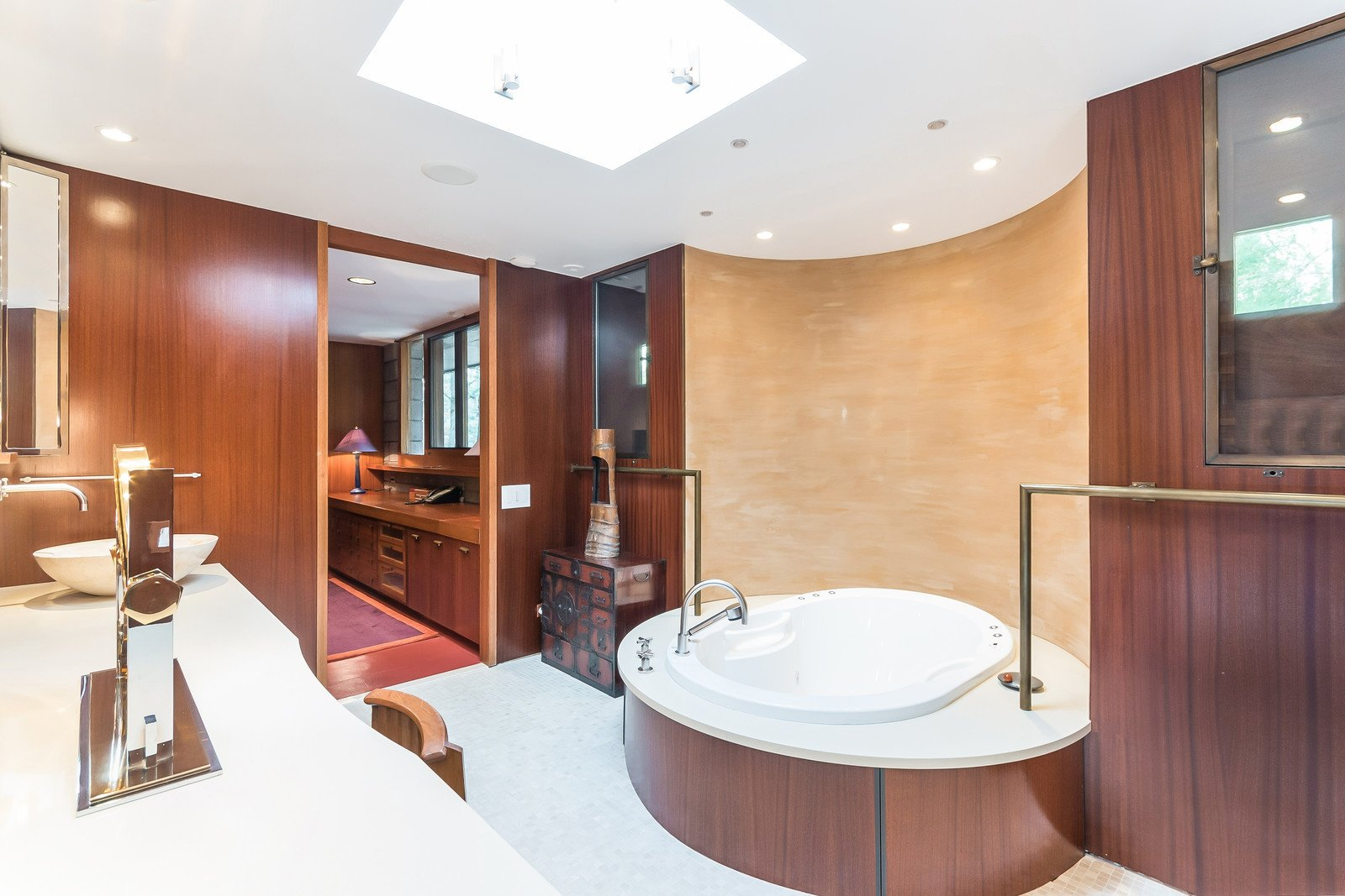 Shown here is one of the double master bathrooms, which holds a new tub that sits in front of a painted plaster wall. The layout and mahogany panels have remained original.   Tirranna
