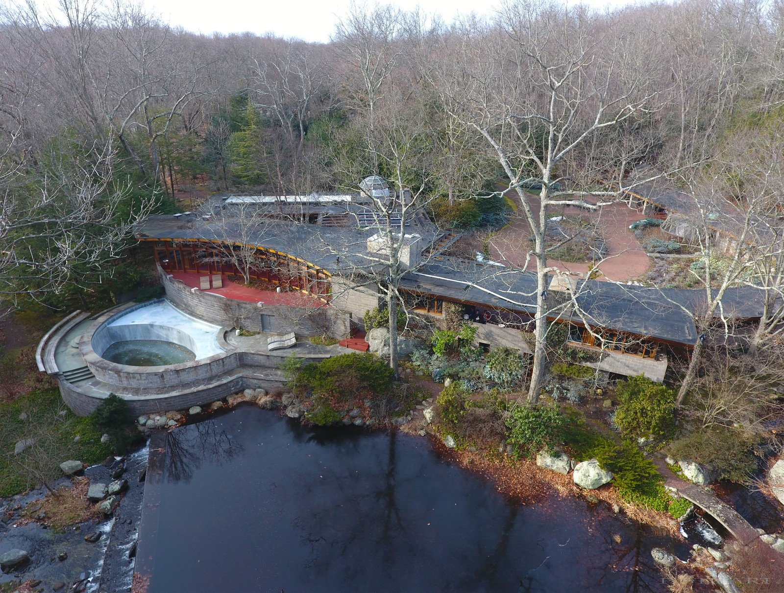 An overhead drone view shows the 15-acre property that also hosts a heated pool, river, tennis court, barn/stable, sculpture path, and rooftop observatory. The original landscaping was designed by Frank Okamura and Charles Middeleer.   Tirranna