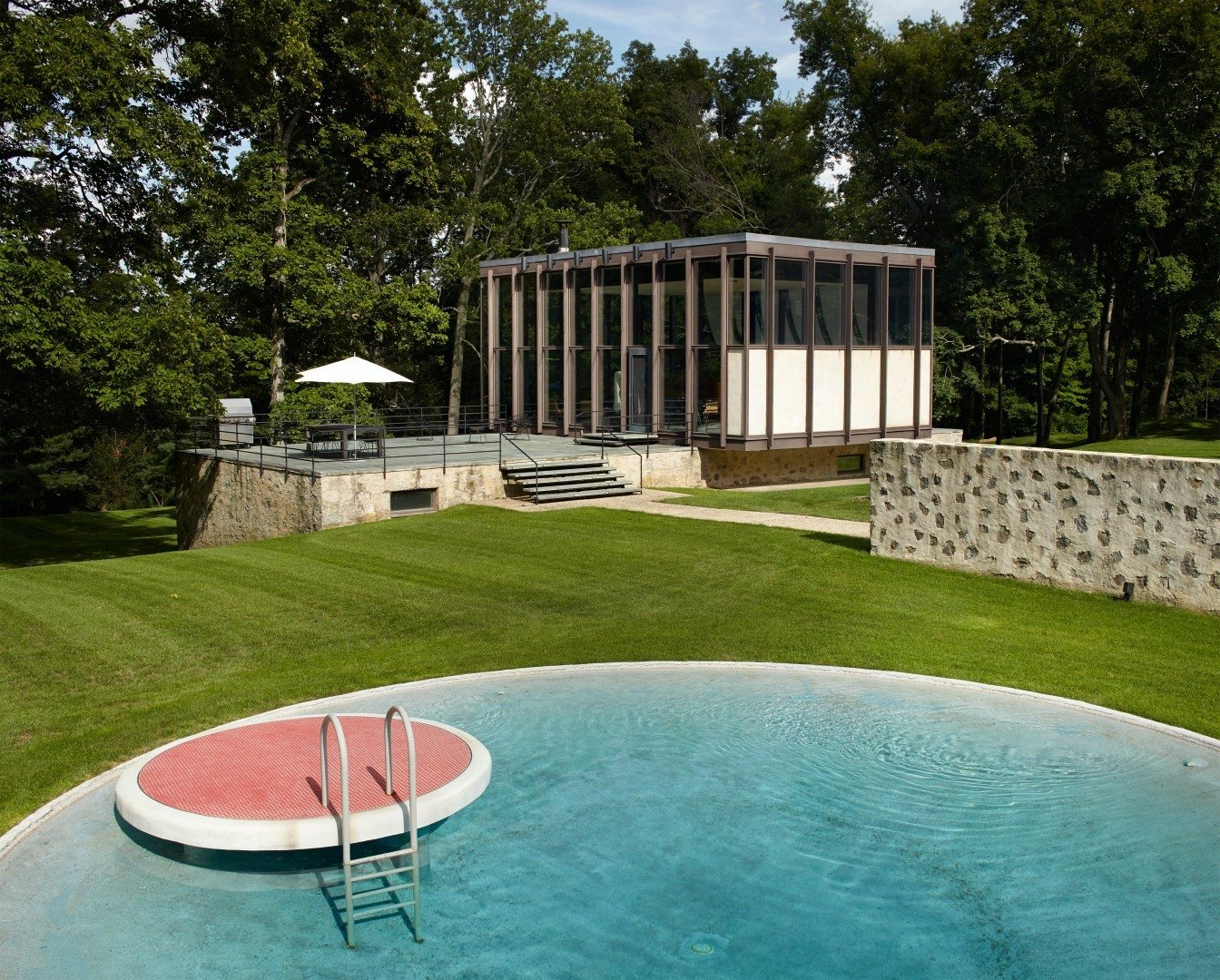 The new pool house and transformed barn that were created by Roger Ferris + Partners during a recent renovation, work together to create a courtyard that borders the original swimming pool. While a very similar circular pool can be found at the Glass House, this one features a lily pad diving platform that's finished with red tile.  Wiley House